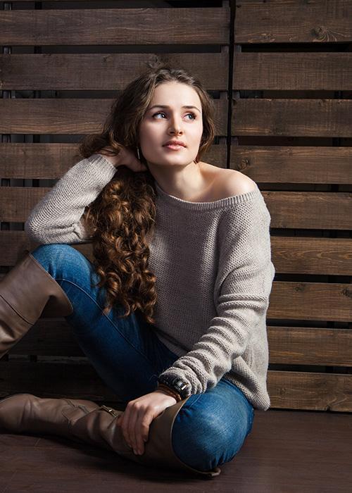 dziewczyna wmodnych ubraniach -  szerokim swetrze, jeansach iwysokich brązowych kozakach