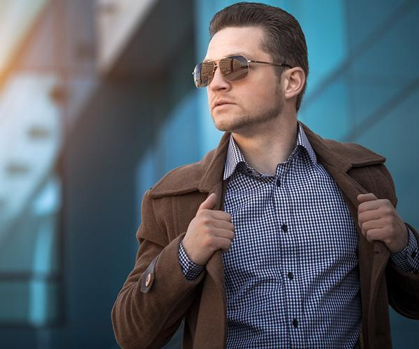 mężczyzna ubrany wmodny płaszcz ikoszulę wdrobną niebieską kratkę